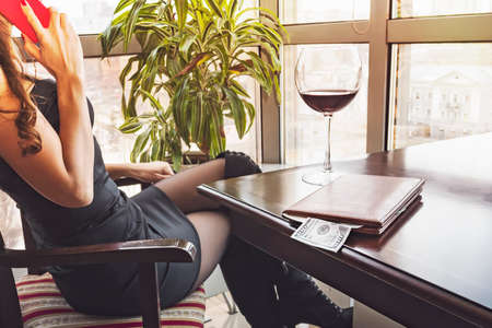 Young pretty woman sitting in the restaurant drinking glass of wine looking out panoramic window with beautiful view of city and talking on phone. 100 dollars in the folder for account on the table.