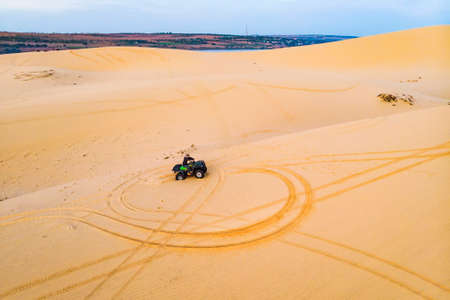 Quad driving people - happy bikers in sand desert.