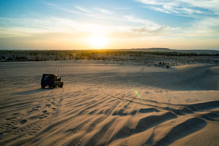 Desert safari with off road 4x4 car in sunlight. colorful sunset in Desert. off-road car rides on the sand in the desert dunes in the rays of the rising sun. Imagens