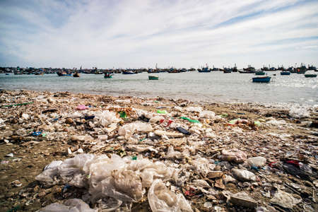 View on a sandy beach near to fishing village with a lot of garbage. Pollution of a coastline. Mui Ne, Vietnam
