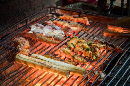 Seafood fried on the grill in a restaurant on the street. Street food in Southeast Asia. Traditional Vietnamese cuisine.