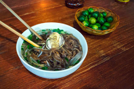 Balut boiled developing duck embryo is a special cuisine in Asia. it's very popular in Philippine, Vietnam, Lao and Cambodia. An exotic soup with Pho noodles on the table in the restaurant Zdjęcie Seryjne