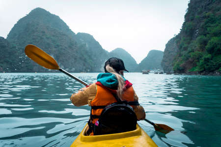 Young beautiful woman floating on a kayak between the rocks sticking out of the sea. The girl rowing the oars on the background of beautiful sea landscape. Water active sports