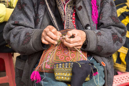 Red dzao ethnic minority woman sewing in Sa Pa, Lao Cai province, Vietnam. an elderly woman sews on the street. Make beautiful embroidery as a souvenir for tourists. hand made