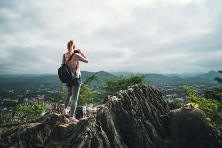 female tourist takes picture of on top of Phousi mountain in Luang Prabang, Laos