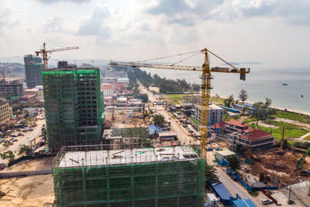 Construction high-rise building by crane in city near sea. construction of expensive hotels in resort town of Sihanoukville, Cambodia. A lot of construction cranes. Scale construction.