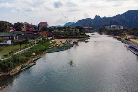 Unidentified tourists are rowing kayak boats in Song River in Vang Vieng, Lao P.D.R. top view, aerial view