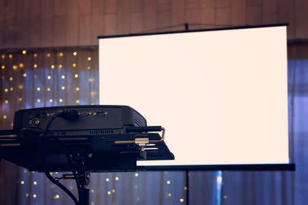 A view to the projection screen equipment at the decorated window curtain background of a banquet hall. Facilities for video and audio projection at a festive event. Show arrangement at a banquet 版權商用圖片