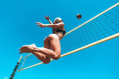 ekstatisches junges Mädchen im Hochfliegen mit einem Ball. Springen Sie von der jungen Frau des Sports, die Volleyball am Meeresstrand gegen den blauen Himmel spielt. Konzept eines gesunden Lebensstils. Blockieren des Balls. Standard-Bild