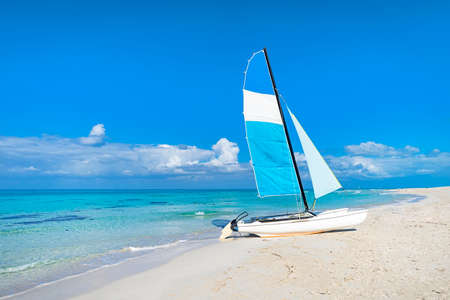 Catamaran landed on the beautiful beach of Varadero in Cuba. Tourist attractions on the Caribbean coast. Sailboat on the background of clear turquoise water in the sea and sky.