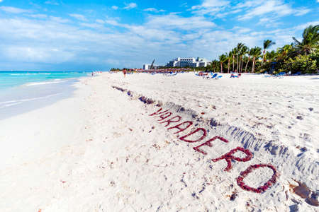 VARADERO written on a sandy beach as the ocean. Varadero, Cuba. name of the resort town on white sand lined with seaweed