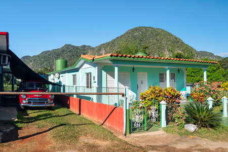 Old fashioned vintage car by the summer colorful house against mountains in the town of Vinales, Cuba. Banco de Imagens