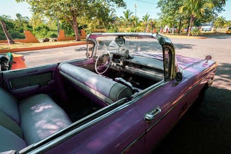 A classic pink retro car is parked on the road in the resort town of Varadero. Cuba.