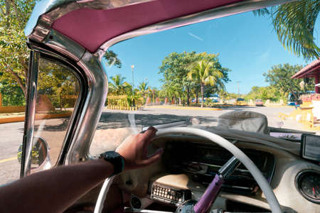 Inside of a vintage pink classic american car in Cuba. driver holds the steering wheel of the old car with his hand. Varadero Фото со стока