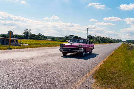 Vintage American retro car on a rural road. Cuba Vinales valley Imagens