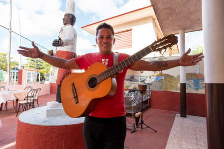 Varadero, Cuba. November 29, 2019: cheerful happy musician with a guitar welcomes guests to his restaurant.