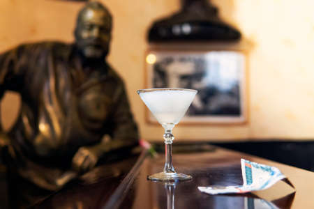 November 26, 2019, Havana, Cuba: Glass of Daiquiri cocktail and statue of American writer Ernest Hemingway in the bar El Floridita in Havanna Editorial