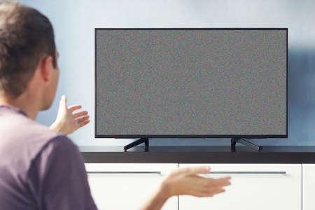 Uomo frustrato seduto sul divano davanti alla televisione senza segnale. giovane ragazzo che guarda emotivamente la TV e agita le mani scontento. Archivio Fotografico