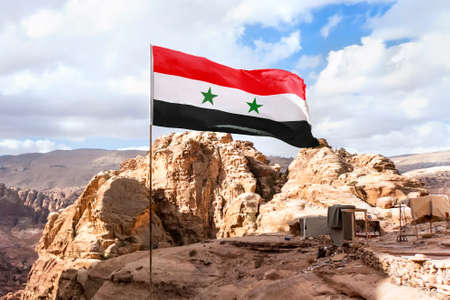 The flag of Syria on a flagpole flutters in the wind against the sky. The Syrian flag is set at a height in the mountains against the backdrop of the nature of the middle East.
