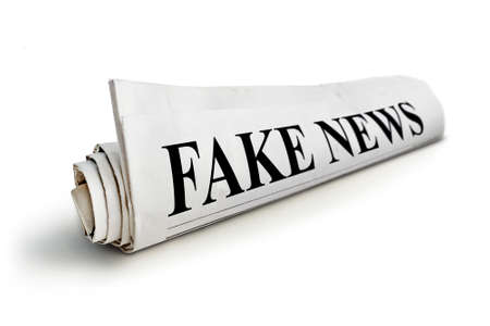 concept of false news. Rolled Up Newspaper with Headline of Fake News Isolated on White Background.