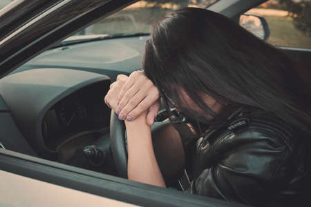 Close up of exhausted brunette woman leaning head on steering wheel. Dark-haired girl puts her head on the steering wheel after car accident. Woman sleeping sitting inside automobile. Waiting in car