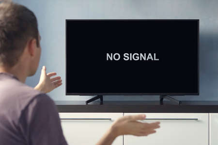 Poor digital TV signal. No signal inscription on the TV screen. The guy is upset about the TV breaking down. Foto de archivo
