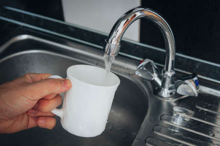 Modern faucet and sink in home kitchen. Man pouring fresh drink to cup. Filling white glass with tap water.
