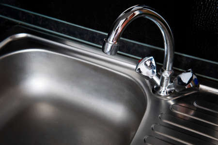 Kitchen silver sink modern decoration house stainless steel. Grey clean sink and faucet for hot source water made of metal on a dark black background. Reklamní fotografie