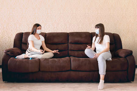 Womens sit on the sofa in the livingroom protected by medical masks at a great distance so as not to infect each other. Maintaining a social distance to protect against viruses. covid-19,