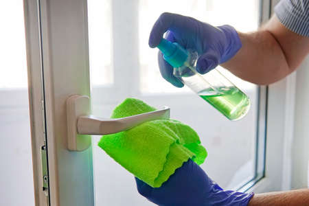 man disinfects door handle with disinfectant liquid. spraying door handle and wiping with a cloth. Disinfection of premises.prevention coronavirus, infectious diseases. Tidying up. window washing.