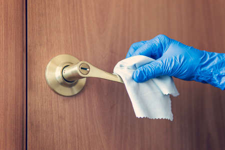 A woman's hand wipes the door handle with a wet rag. The maid is washing the doorknob. Prevention of coronavirus and bacterial infections Archivio Fotografico
