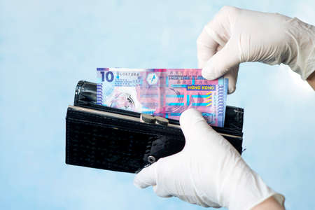 woman taking money out of female wallet wearing rubber gloves to prevent the spread of bacterias or viruses, take shopping during coronavirus pandemic. Microbes on money. Refusal of cash. Stock Photo