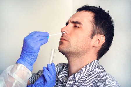 A doctor in a protective suit taking a nasal swab from a person to test for possible coronavirus infection. Nasal mucus testing for viral infections.