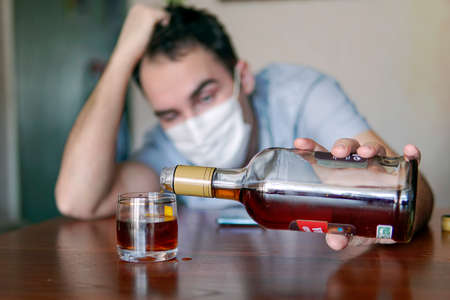 alcoholism, alcohol addiction and people concept - male alcoholic with bottle of rum at home. An unemployed specialist who got drunk alone out of boredom is quarantined in self-isolation. Stock Photo