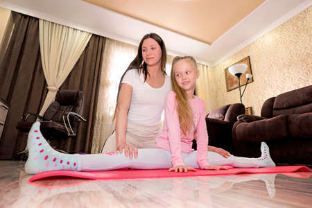 Mother and daughter practicing online yoga lesson at home at quarantine isolation period during coronavirus pandemic. Family doing sport together online from home. Healthy lifestyle. on splits Stockfoto