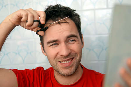 Handsome man cutting his own hair with a scissors and looks in the mirror. self-care in the conditions of global quarantine and closed hairdressers and beauty salons. trim your bangs. stay at home Banque d'images