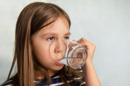 A little girl drinks water from a glass Cup. little girl holding a glass of water. thirst for water