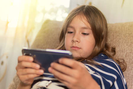 Happy cute little girl playing games on smartphone at home. During the global pandemic, kindergartens and schools are closed and children stay at home. Reklamní fotografie