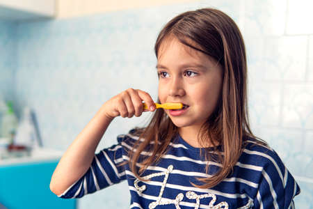 A little girl of Caucasian appearance brushing her teeth with a toothbrush, Hygiene procedures in the morning. Child girl brushing teeth in bathroom 스톡 콘텐츠