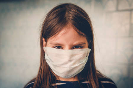 unhappy little girl in a mask. Portrait of an angry girl dissatisfied with self-isolation and quarantine caused by outbreak of covid-19 coronavirus infection 스톡 콘텐츠