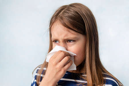 resentment and tears. child is crying and wipes his snot with a white wet napkin. A girl sneezes into a rag on a blue background. An unhealthy child is coughing.