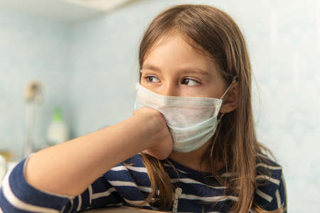 child girl in medical mask. Sad eyes of a girl. . Children in quarantine at home. an unhappy sick girl is sad in self-isolation.