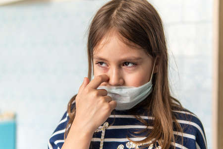 Toddler girl with medical mask on face. Covid19 corona virus outbreak. girl touches face dirty hands, it's not safe. Sad girl is tired of sitting at home on self-isolation quarantine during pandemic.
