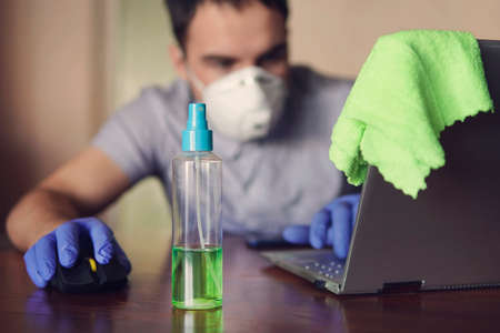 young man wearing medical face mask at work from home office due to corona virus outbreak with laptop on wooden table, remote work against the background of the home environment. 스톡 콘텐츠