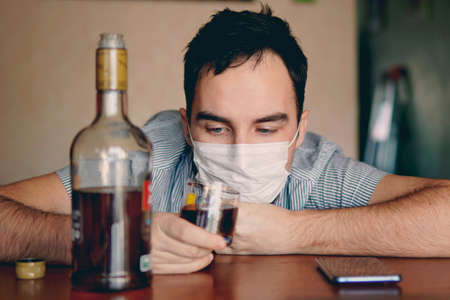 alcoholism, alcohol addiction and people concept - male alcoholic with bottle of rum at home. An unemployed specialist who got drunk alone out of boredom is quarantined in self-isolation. 스톡 콘텐츠