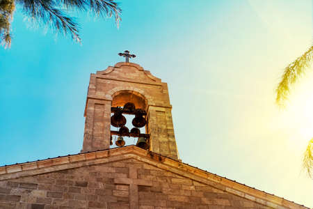 Steeple on top of roof of christian orthodox byzantine Greek church. Big bronze bell, and a big white cross, background view of blue cloudy sky in bright yellow sun