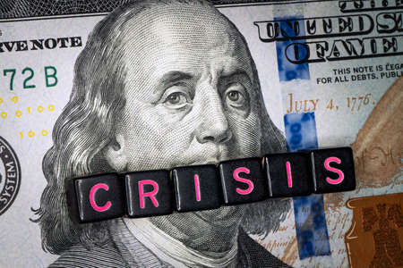 portrait of Benjamin Franklin from hundred-dollar bill with a closed mouth and the caption title CRISIS. global financial economic crisis because of the covid-19 coronavirus pandemic