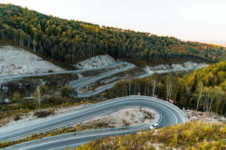 Dangerous road near resort town of Belokurikha. serpentine road in mountains of the Altai on a bright, sunny day, below is a green grass and an asphalt road with a sharp turn leaving behind a mountain