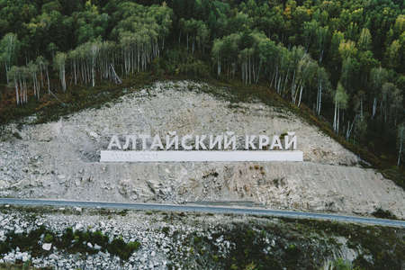 Inscription in Russian language Altai Krai is the name of a region in Western Siberia in Russia. Letters on a rock near the serpentine road. tourist cluster Belokurikha 2