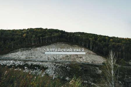 Inscription in Russian language Altai Krai is the name of a region in Western Siberia in Russia. Letters on a rock near the serpentine road. tourist cluster Belokurikha 2